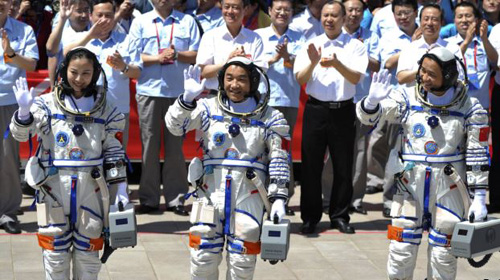 Chinese astronauts (from left) Wang Yaping, Zhang Xiaoguang and Nie Haisheng wave before leaving for the Shenzhou-10 manned spacecraft mission at a satellite launch center in Jiuquan, Gansu Province on June 11, 2013. /Reuters