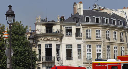 Firefighters are seen working on the roof of the Hotel Lambert, a 17th century mansion overlooking the Seine river, Paris on July 10, 2013. /AP