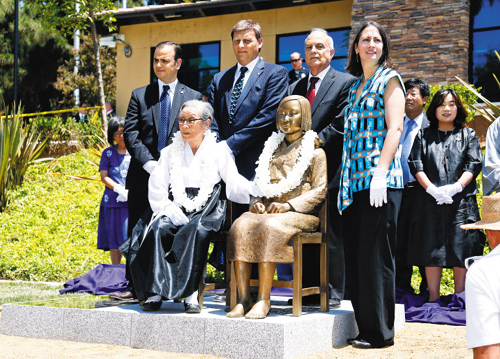 Flanked by Glendale city officials, Kim Bok-dong, a former comfort woman, poses with a statue honoring her fellow victims in a park in Glendale, Los Angeles on Tuesday.