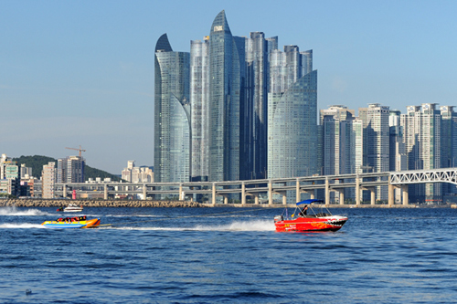A motor boat pulls a banana-shaped boat past Gwangan Bridge.