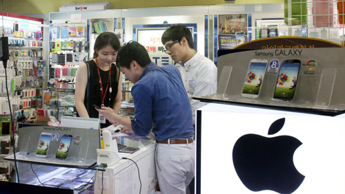 Shoppers look at smartphones at a store in Yongsan on Sunday.