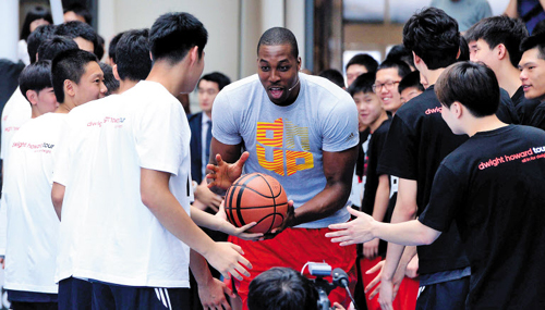 Young Korean students welcome Dwight Howard of the Houston Rockets at a basketball clinic at Time Square plaza in Yeongdeungpo, Seoul on Sunday.