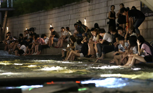 Sleepless people cool themselves in the Cheonggye Stream in Seoul on Sunday.