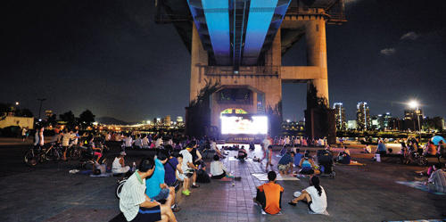 People escape the heat to watch a movie at the Ttukseom Han River Park in Seoul on Friday. /Newsis