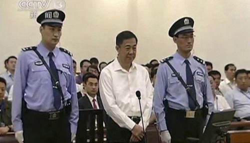 In this image taken from video, disgraced politician Bo Xilai (center) stands in the courtroom, flanked by police guards at Jinan Intermediate Peoples Court in eastern Chinas Shandong province on Aug. 22, 2013. /AP