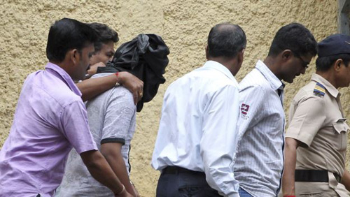 Police officials escort an accused, head covered with black cloth, in the gang rape of a young photojournalist in the Indian financial hub of Mumbai on Aug. 24, 2013. /AP