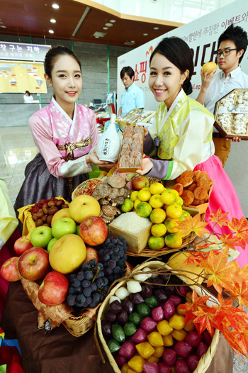 Models in hanbok or traditional Korean dress promote gifts for Chuseok or Korean Thanksgiving at the Seoul Central Post Office on Tuesday. /Newsis