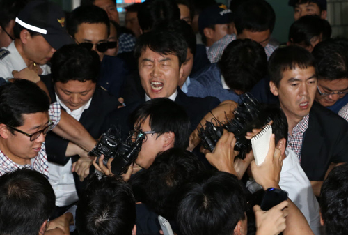 Lawmaker Lee Seok-ki of the leftist Unified Progressive Party shouts as he is surrounded by police officers and reporters after being arrested at the Suwon police station in Suwon, Gyeonggi Province on Thursday.