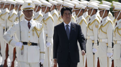 Japans Prime Minister Shinzo Abe reviews the honour guard before a meeting with Japan Self-Defense Forces senior members at the Defense Ministry in Tokyo on Sept. 12, 2013. /Reuters