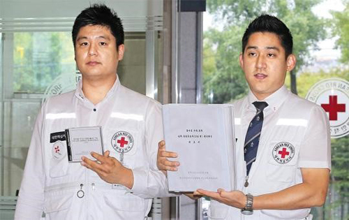 Officials from the South Korean Red Cross show lists of survivors for cross-border family reunions at their headquarters in Seoul on Friday.