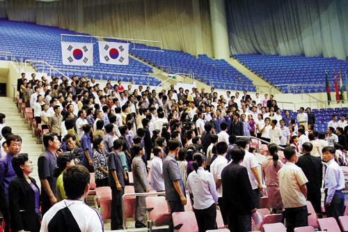 South Korean flags are hoisted above North Korean spectators after athletes from the South won gold and silver medals at the 2013 Asian Cup and Interclub Weightlifting Championships in Pyongyang on Saturday.