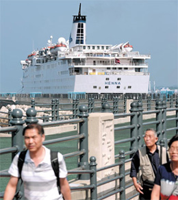 Passengers of the cruise ship Henna leave the ship to fly back to China on Sunday.