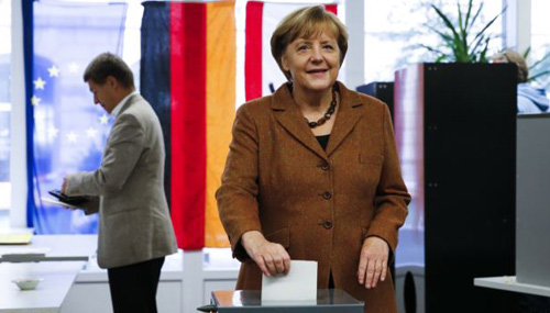 German Chancellor Angela Merkel poses as she casts her ballot during general elections at a polling station in Berlin on Sept. 22, 2013. The person in the background is Merkels husband, Joachim Sauer. /Reuters