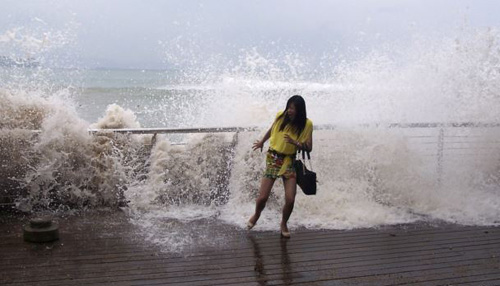 A woman reacts as a storm surge jumps a barrier on the shore as Typhoon Usagi approaches Shenzhen, Guangdong Province on Sept. 22, 2013. /Reuters