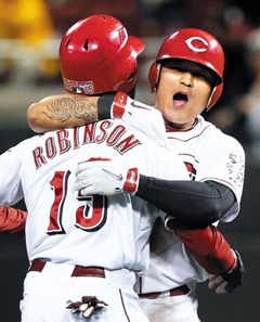 Cincinnati Reds Choo Shin-soo celebrates with Derrick Robinson after Choo hit a single off New York Mets relief pitcher Sean Henn to drive in the winning run in the 10th inning of a baseball game on Monday. /AP
