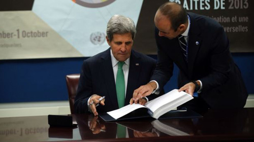 U.S. Secretary of State John Kerry signs the UN Arms Trade Treaty at UN headquarters in New York City on Sept. 25, 2013. Standing beside him is UN Under Secretary-General for Legal Affairs Miguel de Serpa Soares.