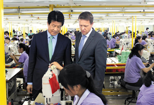 Michael Ertl (right) of German firm Me & Friends tours a shoe factory run by Samduk Tongsang in Kaesong on Thurday. /Courtesy of Samduk Tongsang