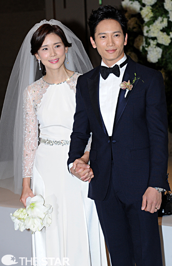 Star couple Lee Bo-young (left) and Ji Sung pose at their wedding at a hotel in Seoul on Friday.