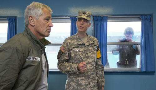 Secretary Hagel listens to U.S. Army Col. James Minnich as a North Korean soldier takes a photograph of the secretary through a window on Sept. 30, 2013. /AP