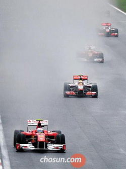 Racing machines drive through the pouring rain during the Formula One Korean Grand Prix in 2010 (file photo).