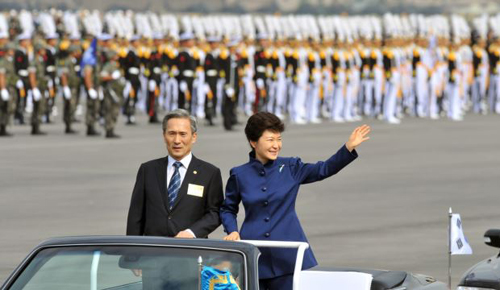 President Park Geun-hye waves as she inspects troops with Defense Minister Kim Kwan-jin during a ceremony marking the 65th anniversary of the founding of South Koreas Armed Forces, Seongnam on Oct. 1, 2013. /AP