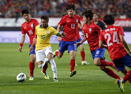 Brazils Neymar fights for the ball with Korean players during a friendly football match at the Seoul World Cup Stadium on Saturday. /Newsis