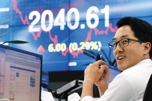 A staffer at KDB Daewoo Securities in Yeouido, Seoul smiles in front of an electronic board showing the KOSPI closing at 2,040.61 points on Thursday.