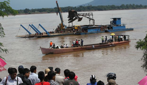 Onlookers watch the search operation for the lost Lao Airlines plane on the banks of the Mekong River in Pakse, Laos on Oct. 17, 2013. /AP