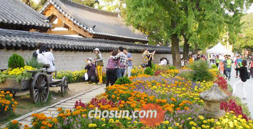 Visitors to a hanok village in Jeongju, North Jeolla Province take photos on Oct. 9, outside Gyeonggijeon where a portrait of the founder of the Chosun dynasty is housed.