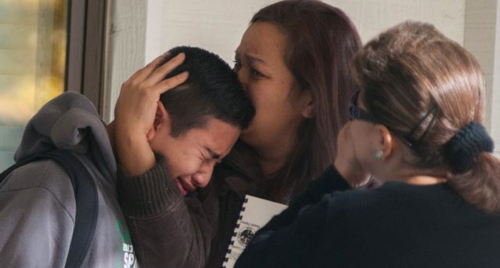 A Sparks Middle School student cries and is comforted after being released from Agnes Risley Elementary School, where some students were evacuated to after a shooting at the school in Sparks, Nevada on Oct. 21, 2013. /AP