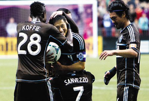 Vancouver Whitecaps Lee Young-pyo smiles as teammate Camilo Sanvezzo (bottom) embraces him after the latter scored a penalty during a game against the Colorado Rapids in Vancouver, British Columbia on Sunday.