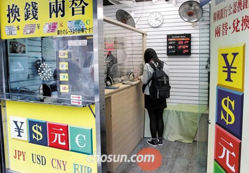 A currency change in the shopping district of Meyong-dong, downtown Seoul on Oct. 22