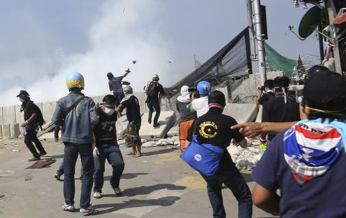 Anti-government protesters throw rocks after riot police fired tear gas at them near the Government House in Bangkok on Dec. 2, 2013.