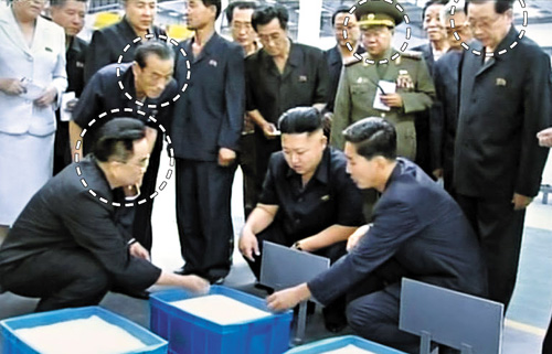 This screen capture from the [North] Korean Central TV shows Ri Yong-ha (front left) and Jang Su-gil, behind Ri, talk with Kim Jong-un at a factory near the Taedong River on Sept. 2, 2012. Jang Song-taek is at back right.