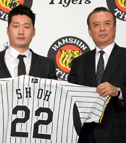 Oh Seung-hwan (left) holds up his Hanshin Tigers uniform with general manager Katsuhiro Nakamura during a signing ceremony in Seoul on Wednesday. /Newsis