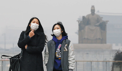Pedestrians wear masks in Gwanghwamun, Seoul on Thursday as the capital is blanketed by toxic haze from China.