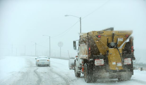 Driver struggles to climb overpass on Hinkleville Road as a snow plow approaches, Paducah, Kentucky on Dec. 6, 2013. /AP