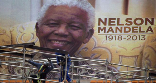 An image of Nelson Mandela is displayed on a digital screen as workers on scaffolding construct a stage ahead of Mandelas national memorial service at First National Bank (FNB) Stadium, also known as Soccer City, in Johannesburg on Dec. 9, 2013. /Reuters