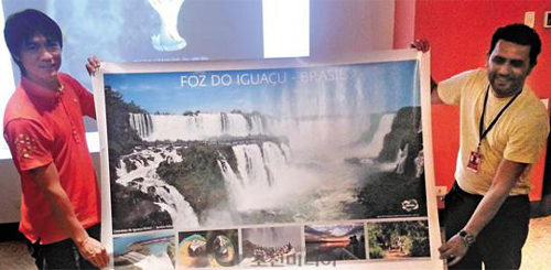 National football team manager Hong Myung-bo (left) holds a poster of the Iguazu Falls, a gift from the city of Foz do Iguaçu in Brazil on Monday.