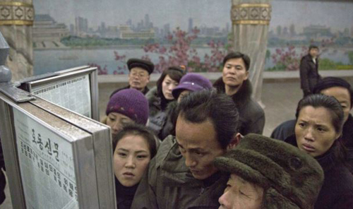 North Korean subway commuters gather around a public newspaper stand on the train platform in Pyongyang on Dec. 13, 2013 to read the headlines about Jang Song-taek, North Korean leader Kim Jong-uns uncle who was executed. /AP