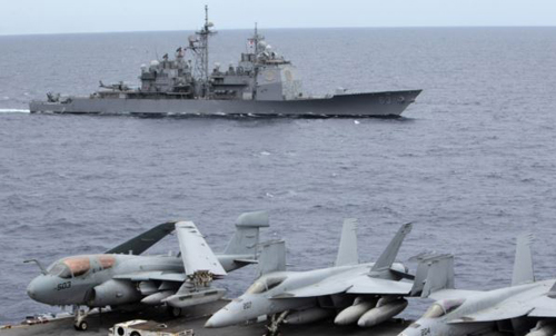 U.S. fighter jets on standby at the upper deck of a USS George Washington aircraft carrier while the USS Cowpens passes by, in the South China Sea, 170 nautical miles from Manila in September 2010. /Reuters