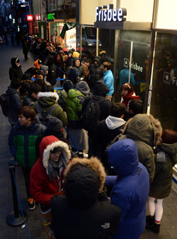 People wait in line to buy the iPad Air and iPad Mini outside an Apple store in Myeong-dong, Seoul on Monday. /Newsis