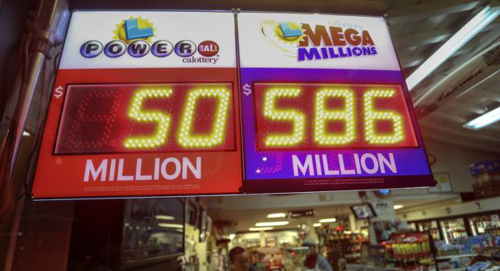 A worker at Nicks Liquor Store sells lottery tickets as a sign shows the Mega Millions jackpot estimated at $586 million in Venice, California on Dec. 16, 2013. /Reuters