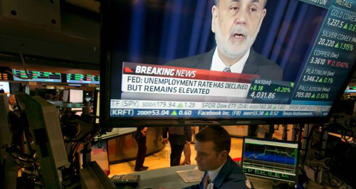 The news conference of Federal Reserve Chairman Ben Bernanke appears on a television screen at a trading post on the floor of the New York Stock Exchange on Dec. 18, 2013. /AP