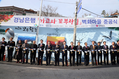 Dignitaries celebrate the completion of a mural project in a poor hillside village in Changwons Masanhappo district, South Gyeongsang Province on Dec. 5.