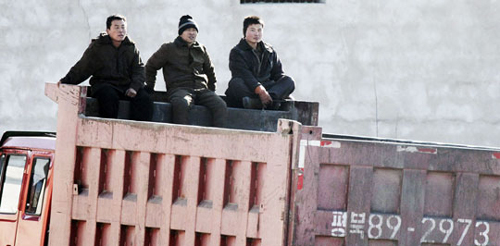 North Koreans sit on back of a truck on the banks of Yalu River on Saturday near the North Korean town of Sinuiju, opposite the Chinese border city of Dandong. /Reuters-Newsis