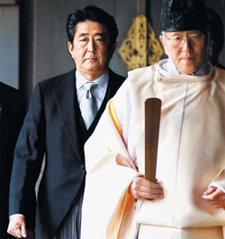 Japans Prime Minister Shinzo Abe is led by a Shinto priest as he visits the Yasukuni Shrine in Tokyo on Thursday. /Reuters-Newsis