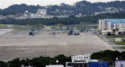 U.S military airplanes and helicopters sit on the airstrip at Futenma Marine Corps Air Station surrounded by houses in Ginowan, Okinawa, Japan. /AP