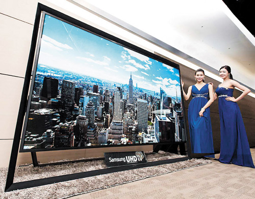 Models show Samsungs new UHD TV, the worlds biggest, in a store in Seoul on Monday. /Newsis