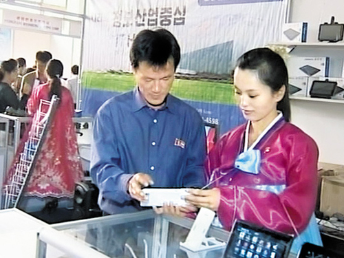 North Koreans look at a tablet PC at an exhibition of products from around the world in Pyongyang in September last year. /[North] Korean Central TV